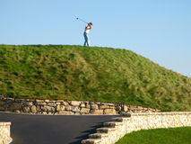 Golfer swinging. A view of a golfer on a hill holding a club back, about to swing at the ball.  A paved walkway with pretty stonework along the side can be seen Stock Photo