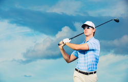 Golfer swinging golf club Stock Photo