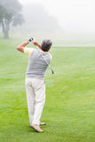 Golfer swinging his club on the course Royalty Free Stock Photography
