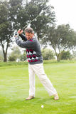 Golfer swinging his club on the course. On a foggy day at the golf course Royalty Free Stock Photography