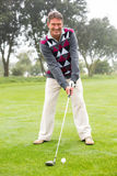 Golfer swinging his club on the course. On a foggy day at the golf course Stock Photography