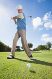 Golfer swinging his club on the course. On a sunny day at the golf course Royalty Free Stock Images