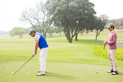 Golfer swinging his club with friend behind him. At the golf course Stock Photo