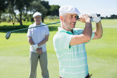 Golfer swinging his club with friend behind him. On a sunny day at the golf course Royalty Free Stock Photo