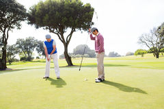 Golfer swinging his club with friend. At the golf course Stock Photography