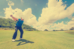 Golfer swinging his gear and hit the golf ball Stock Image