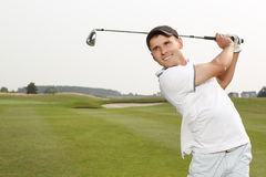 Golfer swinging his niblick out. On the course Royalty Free Stock Photo
