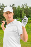 Golfer in a  T-shirt and a baseball cap with golf club. Golfer in a white T-shirt and a baseball cap with golf club Stock Photography