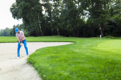 Golfer taking a bunker shot Royalty Free Stock Image