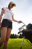 Golfer taking out iron from golf bag. Stock Photo