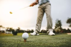 Golfer taking a shot at golf course driving range. Golf ball on tee with man blurred at back about to make a shot at golf course. Focus on golf ball on tee with stock image