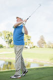 Golfer taking a shot and smiling Royalty Free Stock Photos
