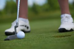 Golfer Tapping In. Photo of a golfer stepping up to his ball just inches from the hole, tapping in stock image
