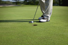 Golfer tapping in short putt. Shown from knees down on defocused background Stock Image