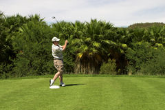 Golfer on the tee. Golfer turning after the shot from the tee box. Golf club is still in motion after the shot royalty free stock image