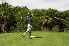 Golfer on the tee box. Golfer hitting the ball from the tee box. Golf club is slightly in motion Stock Photo
