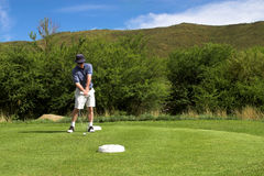 Golfer on the tee box. Golfer hitting the ball from the tee box. Hands and club are in motion Stock Photos