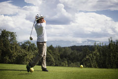 Golfer teeing off. Male golf player teeing off golf ball from tee box, wonderful cloud formation in background stock photo