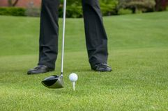 Golfer teeing off on the golf course royalty free stock photography