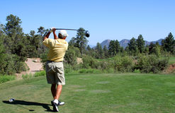 Golfer teeing off in the mountains. Over a hazard using a driver Royalty Free Stock Photo