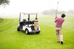 Golfer teeing off next to his golf buggy Stock Photo