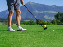 Golfer teeing off. Photo of a male golfer teeing off on a golf course on a beautiful day stock images