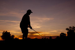 Golfer Teeing Off at Sunset. A golfer tees off while silhouetted in the sunset Stock Image