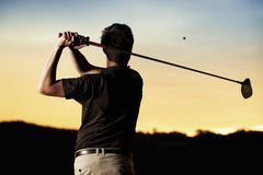 Golfer teeing off at sunset. Close up professional golf player in black shirt teeing-off ball in twilight, view from behind stock image