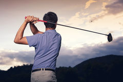 Golfer teeing off at sunset. Close up of professional golf player in blue shirt teeing-off ball at sunset, view from behind stock image