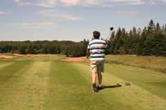 Golfer Tees Off. On a beautiful summer day Royalty Free Stock Image
