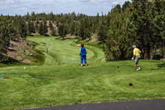 Golfer tees off. REDMOIND, OREGON - MY 25, 2013 - Golfer tees off down a long fairway  in the high desert of central Oregon, near Redmond Stock Images