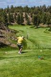 Golfer tees off. REDMOND, OREGON - MY 25, 2013 - Golfer tees off down a long fairway  in the high desert of central Oregon, near Redmond Stock Image