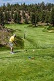 Golfer tees off. REDMOND, OREGON - MY 25, 2013 - Golfer tees off down a long fairway  in the high desert of central Oregon, near Redmond Stock Images