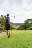 Golfer tees off from tee box to fairway. Golfer hits golf ball, teeing off from the tee box to the fairway under cloudy skies Royalty Free Stock Image