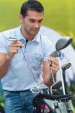 Golfer tidying up golf clubs. Golfer tidying up his golf clubs Stock Photos
