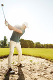 Golfer about to hit ball out of a sand bunker. Male golfer about to hit ball out of a sand bunker while playing on a green course Stock Photos