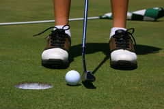 A golfer about to putt. Close-up of a young golfer about to hit in a short putt with flag visible in the background Stock Photo