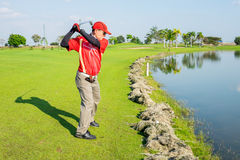 Golfer try to play the ball on cut grass Stock Photography