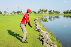 Golfer try to play the ball on cut grass Stock Images