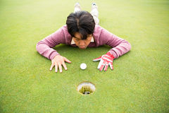 Golfer trying to flick ball into hole Stock Photo