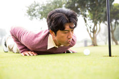 Golfer trying to flick ball into hole Royalty Free Stock Images