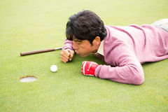 Golfer trying to flick ball into hole Stock Image