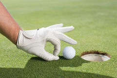 Golfer trying to flick ball into hole. On a sunny day at the golf course Royalty Free Stock Image