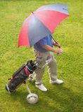 Golfer and umbrella. Sun and Rain a golfer caught in a spring shower.waiting for rain to pass Royalty Free Stock Images