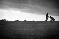 Golfer under moody sky stock photo