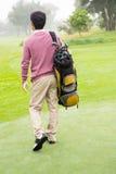 Golfer walking away holding golf bag Royalty Free Stock Images