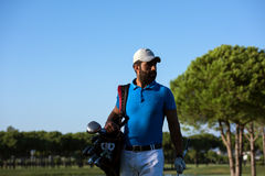 Golfer  walking and carrying bag Stock Photos