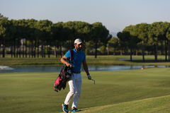 Golfer  walking and carrying bag Royalty Free Stock Image