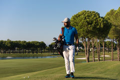 Golfer  walking and carrying bag Royalty Free Stock Images