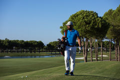 Golfer  walking and carrying bag Stock Photo